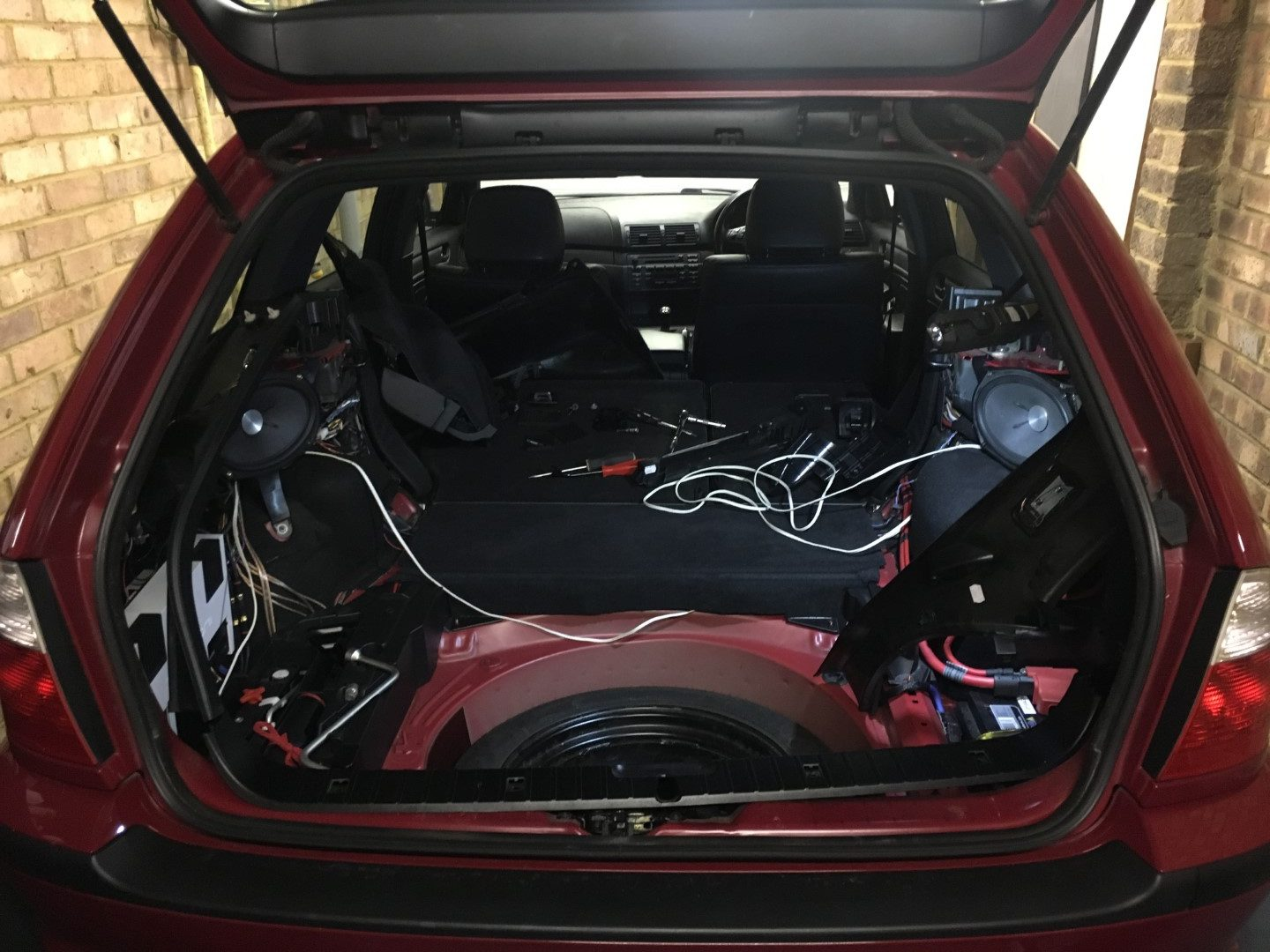 Red car boot with trim removed revealing the installation of two Genesis 6x9 sub woofers